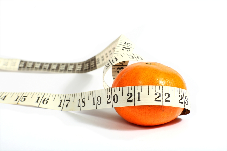 Photo of an orange with measuring tape around it, symbolizing dieting.