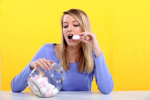 A woman eats marshmallows from a jar.