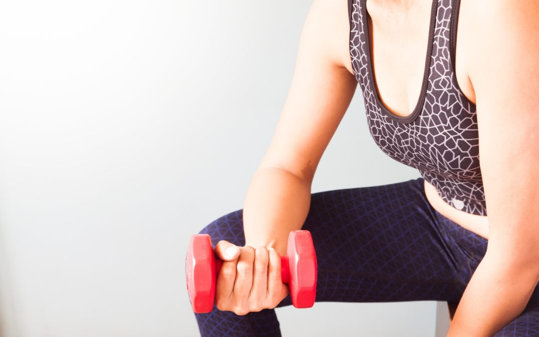 Woman holding red dumbbells to illustrate How Do You Get Rid Of Loose Skin After Weight Loss Surgery