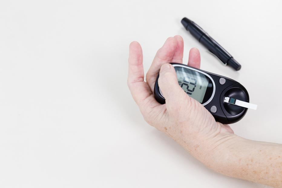 Elderly hands holding blood sugar level machine for diabetes.