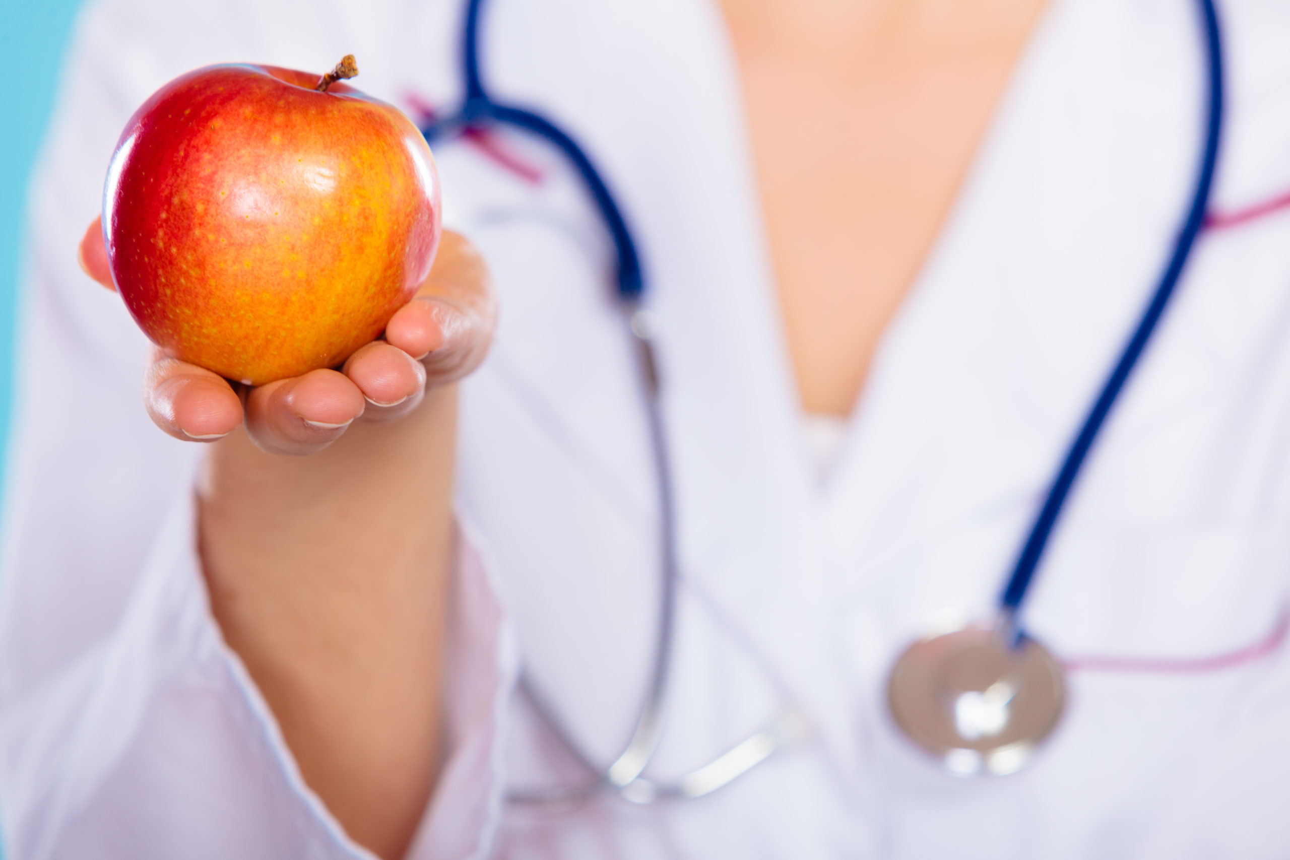 Nutritionist holding apple in her hand