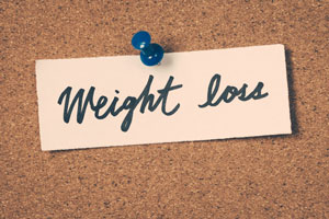 "A note reading ""Weight loss"" is seen pinned to a bulletin board."
