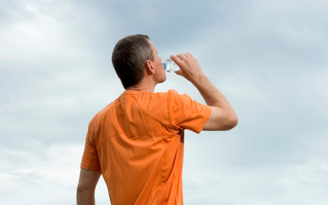 Man in orange shoirt drinking water from a bottle
