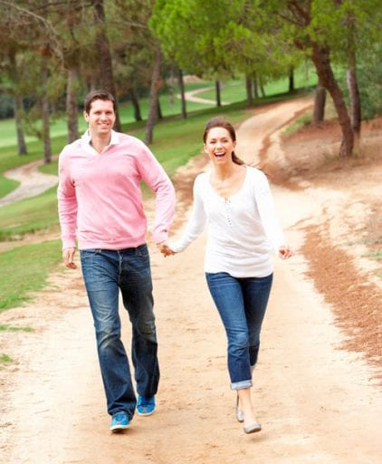 Four low impact exercises for weight loss. A couple is seen walking on a trail.