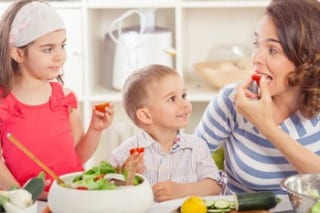 A mother and her two young children are seen eating fresh vegetables.