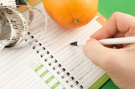 writing in a diet and nutrition journal with orange and tape measure to the side