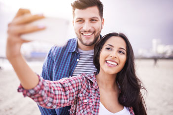 A young couple smiles and poses on the beach for a selfie.