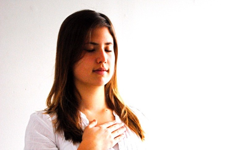 Woman meditating with hand on her upper chest