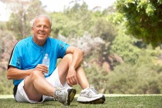 older man drinking water after enjoying exercise