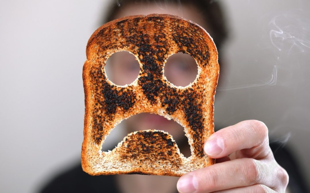 Person holding up piece of toast with unhappy face cut out.