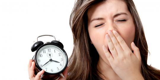 a woman yawning and holding an alarm clock