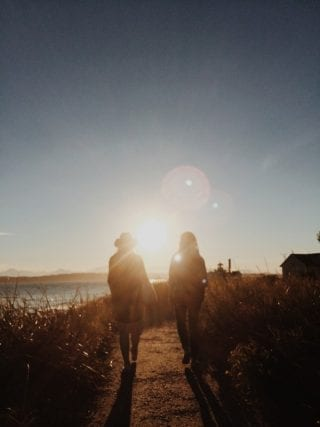 two women on a walk at sunset